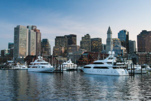 A view of the Boston skyline and Harbour taken from a boat at sunset. Yachts are visible in the foreground.