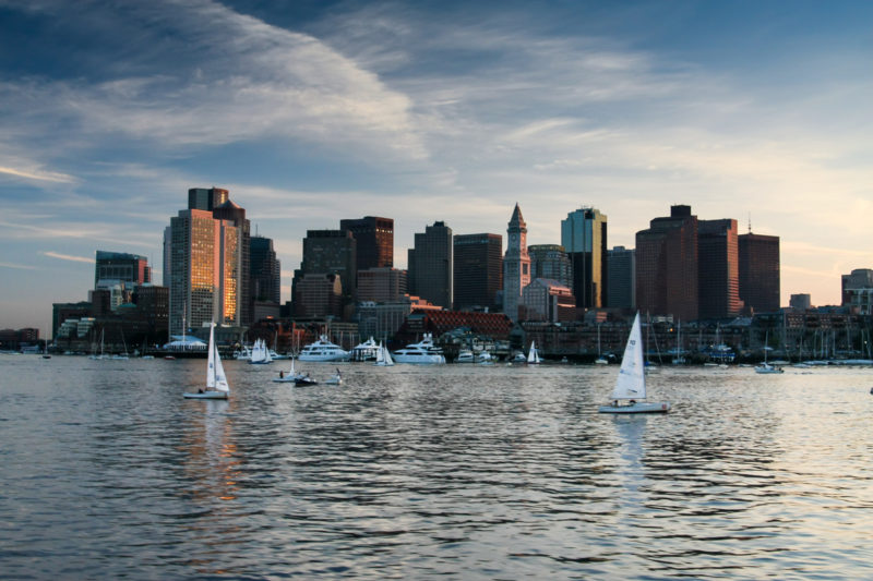 A view of the Boston skyline and Harbour taken from a boat at sunset. Boats are sailing on the water in the foreground.
