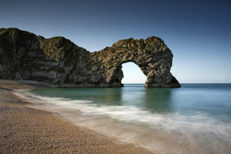 Long exposure of Durdle Door during the day captured the movement of a breaking wave in the foreground.
