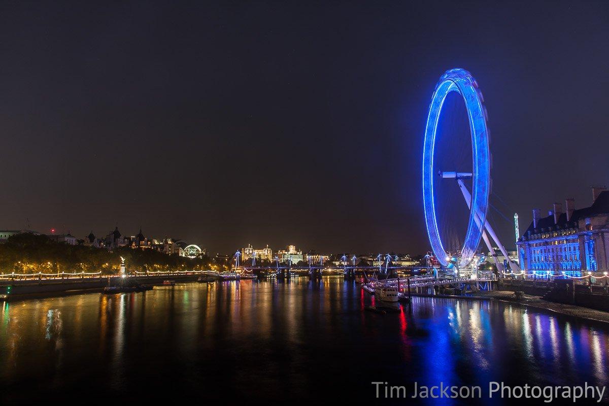 London Eye at Night with reflections of the lights in the water.