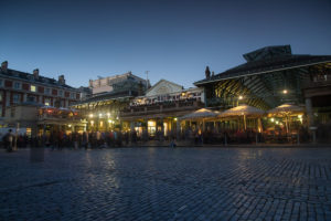 Covent Garden in London at Dusk with a crowd gathering to the left to watch the street performers.